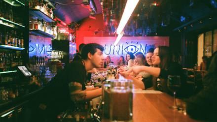 Personas en la barra de un bar.
